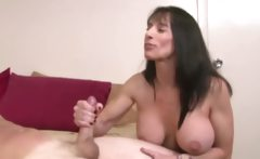 Milf has a firm grip on his hard dick as she jerks him off
